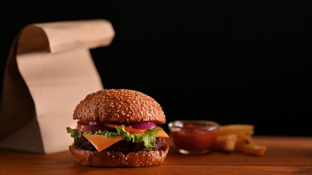Burgery wołowe na drewnianym stole podawane z keczupem i frytkami, czarna ściana