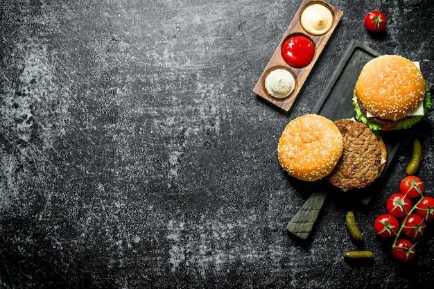 Burgery z frytkami, korniszonami, pomidorami i różnymi sosami. na tle rustykalnym
