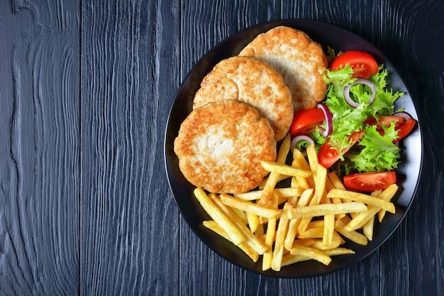 Burgery z indyka z sałatką z pomidorów i masywnymi frytkami na czarnym talerzu na drewnianym stole, widok z góry, flatlay, wolne miejsce na tekst