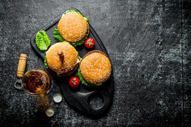 Burgery z nożem i piwem w szklance na czarnym rustykalnym stole.