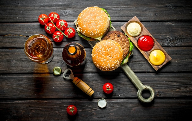 Burgery z piwem w butelce i kieliszku. na czarnym drewnianym stole