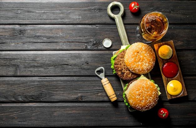 Burgery z piwem w szklance i różnymi sosami. na drewnianym tle