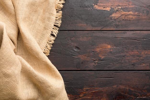 Burlap hesjan grabije płótno na drewnianym stołowym tle z bezpłatną przestrzenią.
