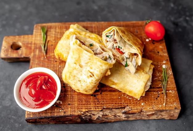 Burrito owija się kurczakiem i warzywami na tle betonu, meksykańskiej shawarma