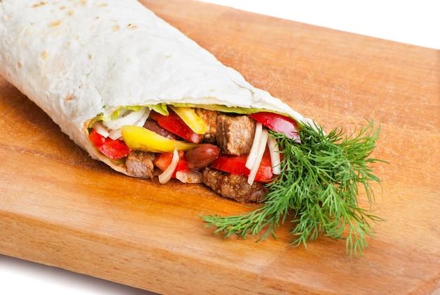 Burrito wołowe z żółtą i czerwoną papryką, cebulą i pomidorem na talerzu