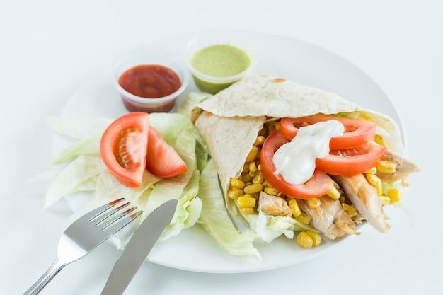 Burrito wrap z pomidorami, kukurydzą, sałatą, kurczakiem, majonezem i sosami z białym tłem