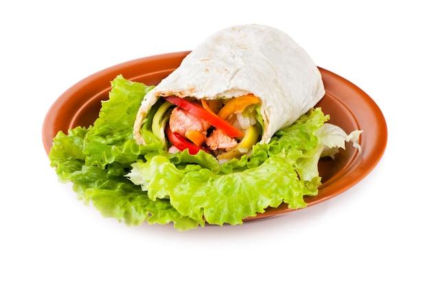 Burrito z łososiem, żółtą, zieloną i czerwoną papryką oraz pomidorem na talerzu