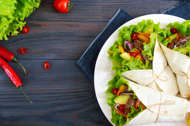 Burrito z posiekanym mięsem, awokado, warzywami, ostrą papryką na talerzu na ciemnym tle drewniane. faszerowana tortilla. tradycyjna meksykańska przekąska. widok z góry.