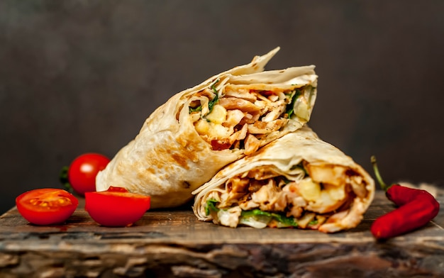 Burrito zawija się kurczakiem i warzywami na desce do krojenia, na tle betonowej meksykańskiej shawarmy
