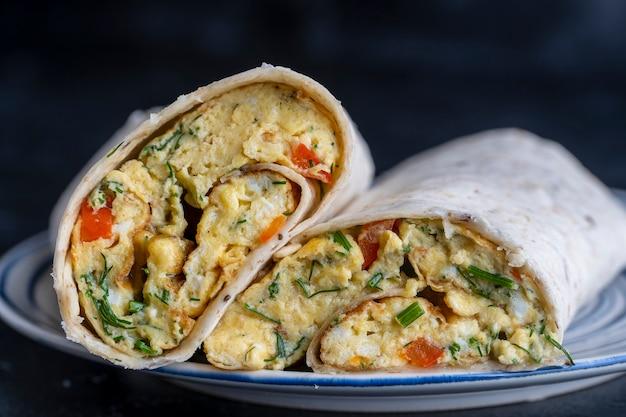 Burrito zawija się z omletem jajecznym i warzywami w chlebku pita. ścieśniać