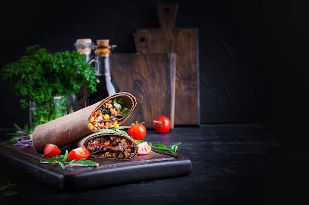 Burritos okłady z wołowiną i warzywami na ciemnym tle drewnianych. burrito wołowe, meksykańskie jedzenie.