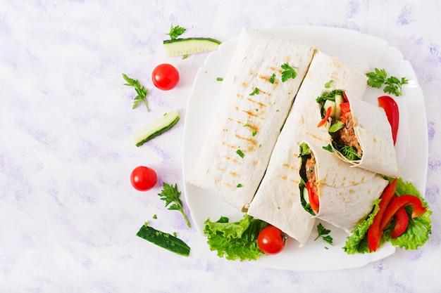Burritos zawija mieloną wołowinę i warzywa. leżał płasko. widok z góry