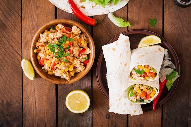 Burritos zawija mięso z kurczaka, kukurydzę, pomidory i paprykę na drewnianym stole. widok z góry