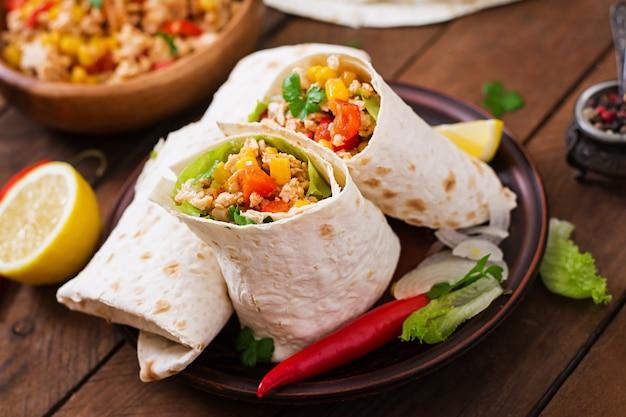 Burritos zawija mięso z kurczaka, kukurydzę, pomidory i paprykę na drewnianym stole