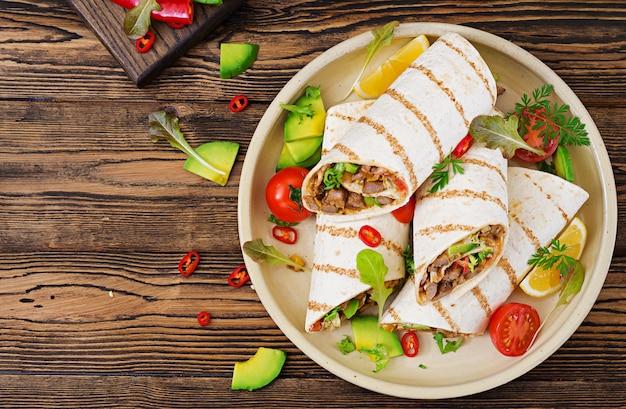 Burritos zawija wołowinę i warzywa na drewnianym stole. burrito wołowe, meksykańskie jedzenie. kuchnia meksykańska. widok z góry.