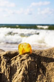 Bursztyn w piasku na tle morskich fal i błękitnego nieba