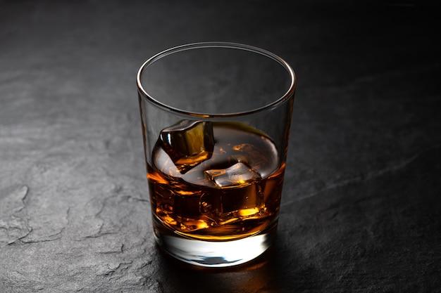 Bursztynowa whisky z kostkami lodu w starym szkle na czarnym kamiennym stole z odbiciem studyjnym
