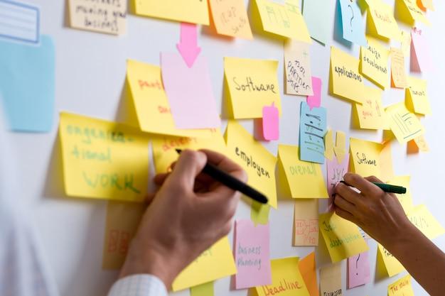 Burza mózgów ludzi biznesu piszących notatki na naklejkach. zespół pracuje nad projektem.