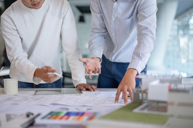 Burza mózgów praca zespołowa architektów omawiająca, projektująca i szkicująca projekt budowy budynku.