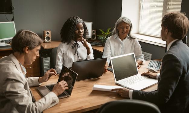 Burza mózgów pracowników grupy diverse pracujących razem nad nowym projektem biznesowym. młoda afrykańska dziewczyna, starsza siwowłosa azjatka i dwóch młodych mężczyzn rasy kaukaskiej dzielą się swoimi pomysłami