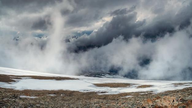 Burza na szczycie góry. wspaniały dramatyczny krajobraz z dużymi ośnieżonymi szczytami górskimi nad niskimi chmurami. atmosferyczne duże szczyty górskie śniegu w zachmurzonym niebie.