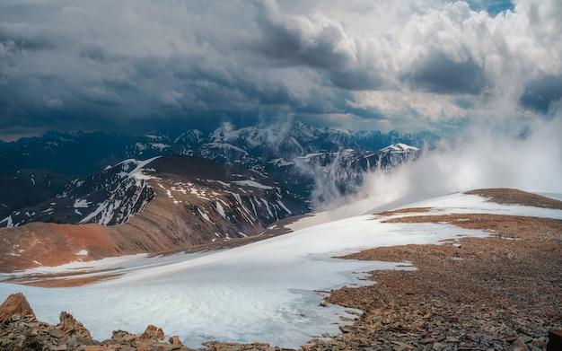 Burza śnieżna na szczycie góry. wspaniały dramatyczny krajobraz z dużymi ośnieżonymi szczytami górskimi nad niskimi chmurami. atmosferyczne duże szczyty górskie śniegu w zachmurzonym niebie.