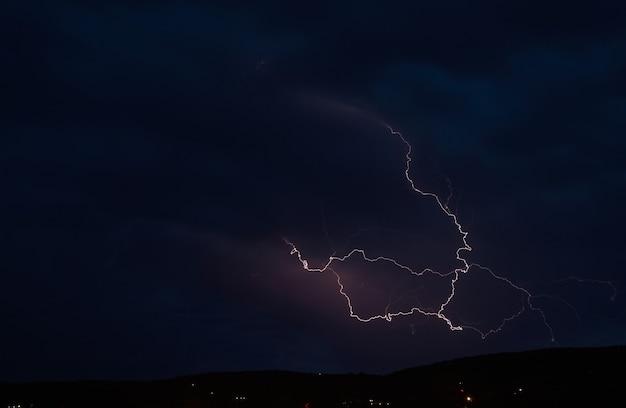 Burza z piorunami na ciemnym chmurnym niebie oświetlonym blaskiem błyskawicy, zjawisko naturalne
