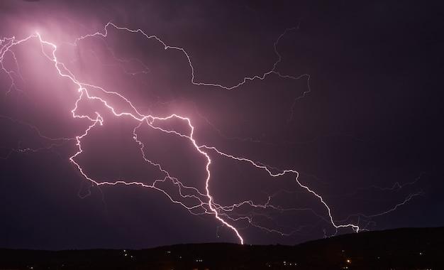 Burza z piorunami na ciemnym chmurnym niebie oświetlonym blaskiem błyskawicy