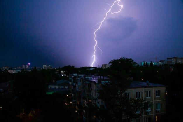 Burza z piorunami nad dachami miasta na nocnym niebie