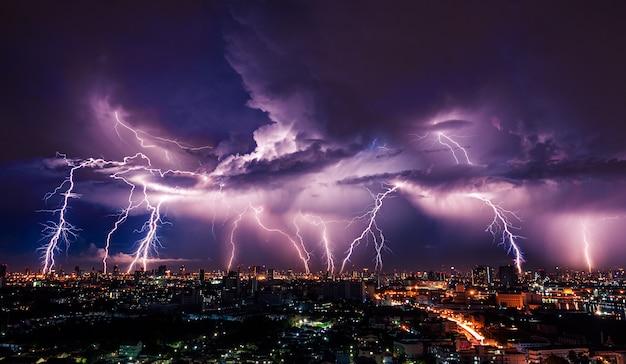Burza z piorunami nad miastem w fioletowym świetle