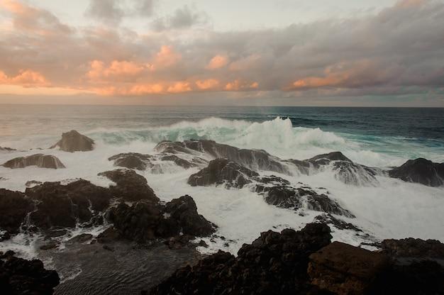 Burzowe lazurowe morze i wiele skał pod zachmurzonym niebem podczas zachodu słońca w letni wieczór