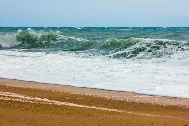 Burzowy morze i niebieskie niebo, biała morze piana na żółtej piaskowatej plaży.