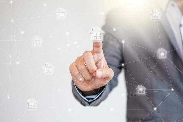 Business manager dotykając sieci ikon domowych w celu rozszerzenia nieruchomości i rozwoju nieruchomości