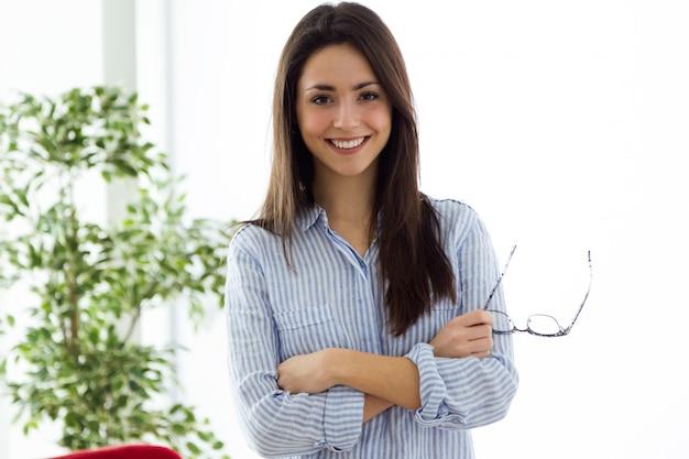 Business młoda kobieta spojrzenie na aparat fotograficzny w biurze.