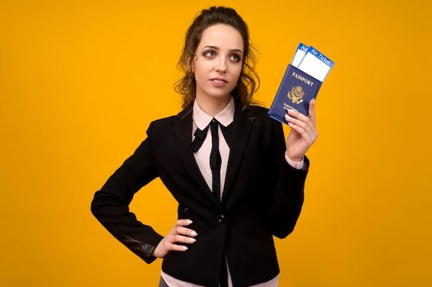 Business woman holding bilety i paszport na żółtym tle studio