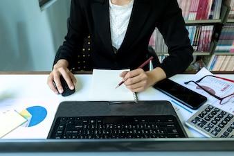 Business woman Makro ręcznie z papieru pisania na wykresie, przy użyciu komputera przenośnego notebooka.