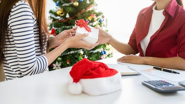 Business woman manager dając prezent swoim kolegom w ostatnim dniu roboczym. młodzi kreatywni ludzie świętują wakacje w nowoczesnym biurze. wesołych świąt i szczęśliwego nowego roku.