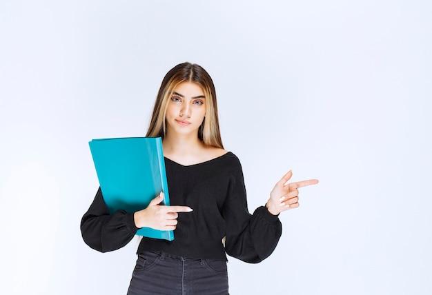 Businesslady trzyma niebieską teczkę i wskazując na swojego kolegę. zdjęcie wysokiej jakości