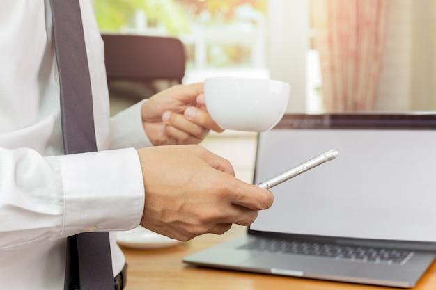 Businessmans ręka trzyma telefon i filiżankę kawy w jego biurze