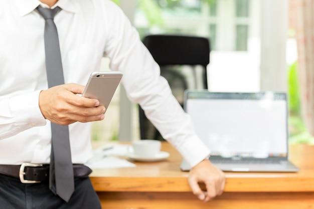 Businessmans ręki mienia telefon komórkowy z laptopem na drewnianym biurku