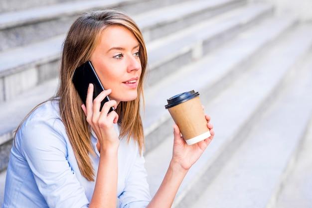 Businesswoman bior? c kaw? i przy u? yciu smartfona.