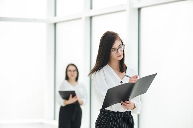 Businesswoman czytając dokument biznesowy, stojąc w hali biura