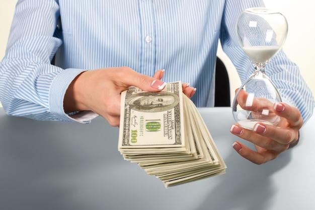 Businesswoman gospodarstwa dolarów i klepsydry. pani trzyma klepsydrę i pieniądze. uważaj na ryzyko. uważaj na termin.