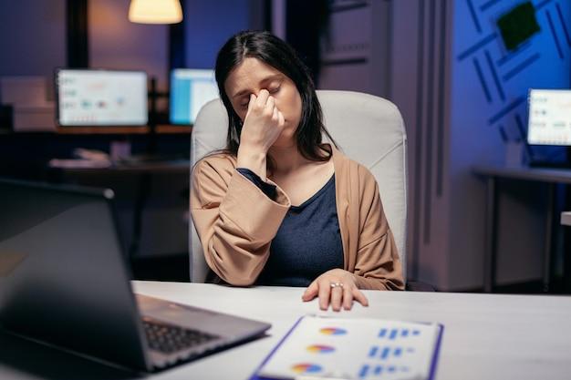Businesswoman ma migrenę w trakcie nadgodzin, aby praca była w terminie. pracownik zasypiający samotnie do późnych godzin nocnych w biurze dla ważnego projektu firmy.