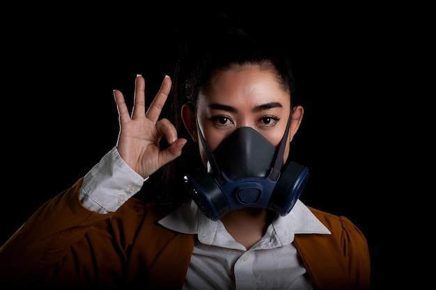 Businesswoman młodej kobiety azji zakładającej maskę n95 do respiratora w celu ochrony przed unoszącymi się w powietrzu chorobami układu oddechowego ręka kobiety znak ok