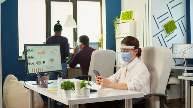 Businesswoman na czacie przy użyciu telefonu w pokoju biurowym, siedząc przy biurku, nosząc maskę i przyłbicę, podczas gdy zespół robi stategy. wieloetniczni współpracownicy pracujący z poszanowaniem dystansu społecznego w firmie finansowej