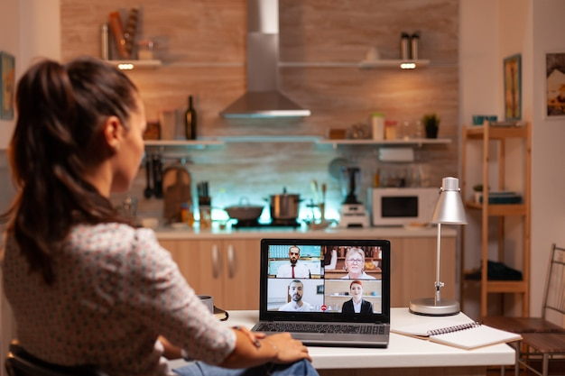 Businesswoman o wideokonferencji z klientami o północy z domu. spotkanie firmowe z wykorzystaniem nowoczesnych technologii, laptop późno w nocy, technika, agencja, doradca, praca, dyskusja.