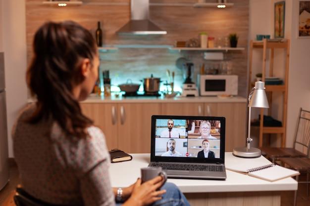 Businesswoman o wideokonferencji z zespołem o północy za pomocą laptopa w domowej kuchni. spotkanie firmowe z wykorzystaniem nowoczesnych technologii, laptop późno w nocy, tech, agencja, doradca, praca, dyskusja