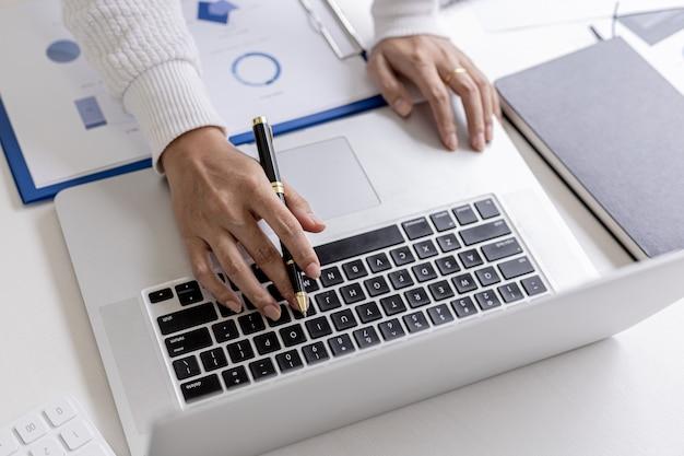 Businesswoman pisząc na laptopie rozmawia z pracownikiem za pomocą komunikatora w laptopie, aby zapytać o finanse firmy. pojęcie wykorzystania technologii do wspomagania komunikacji.