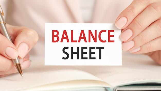 Businesswoman pisze w zeszycie ze srebrnym piórem i ręką trzymać kartę z tekstem: bilans